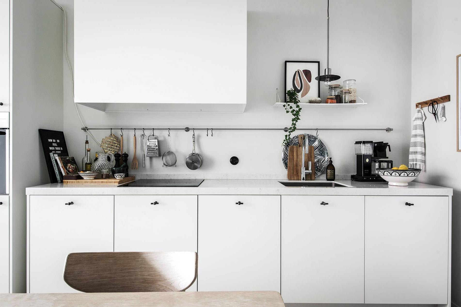 Tủ bếp được thiết kế với tone màu trắng và các kệ treo đơn giản, gọn gàng cho căn hộ chung cư 90m2