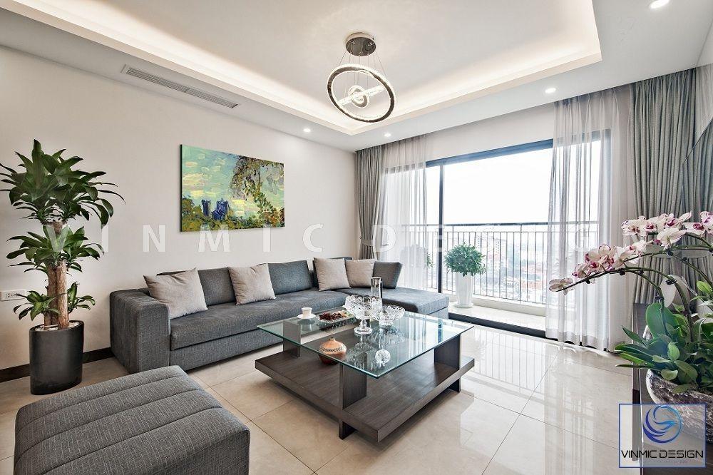 Thi công nội thất phòng khách nổi bật với bộ sofa nỉ tone màu ghi đẹp kết hợp trang trí cây cảnh cho căn hộ 90m2