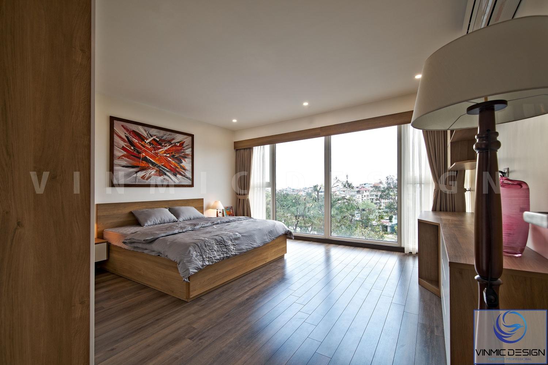 Giường phòng ngủ được thiết kế khá đơn giản, đầu giường được để công, gam màu chủ đạo là xám và nâu.